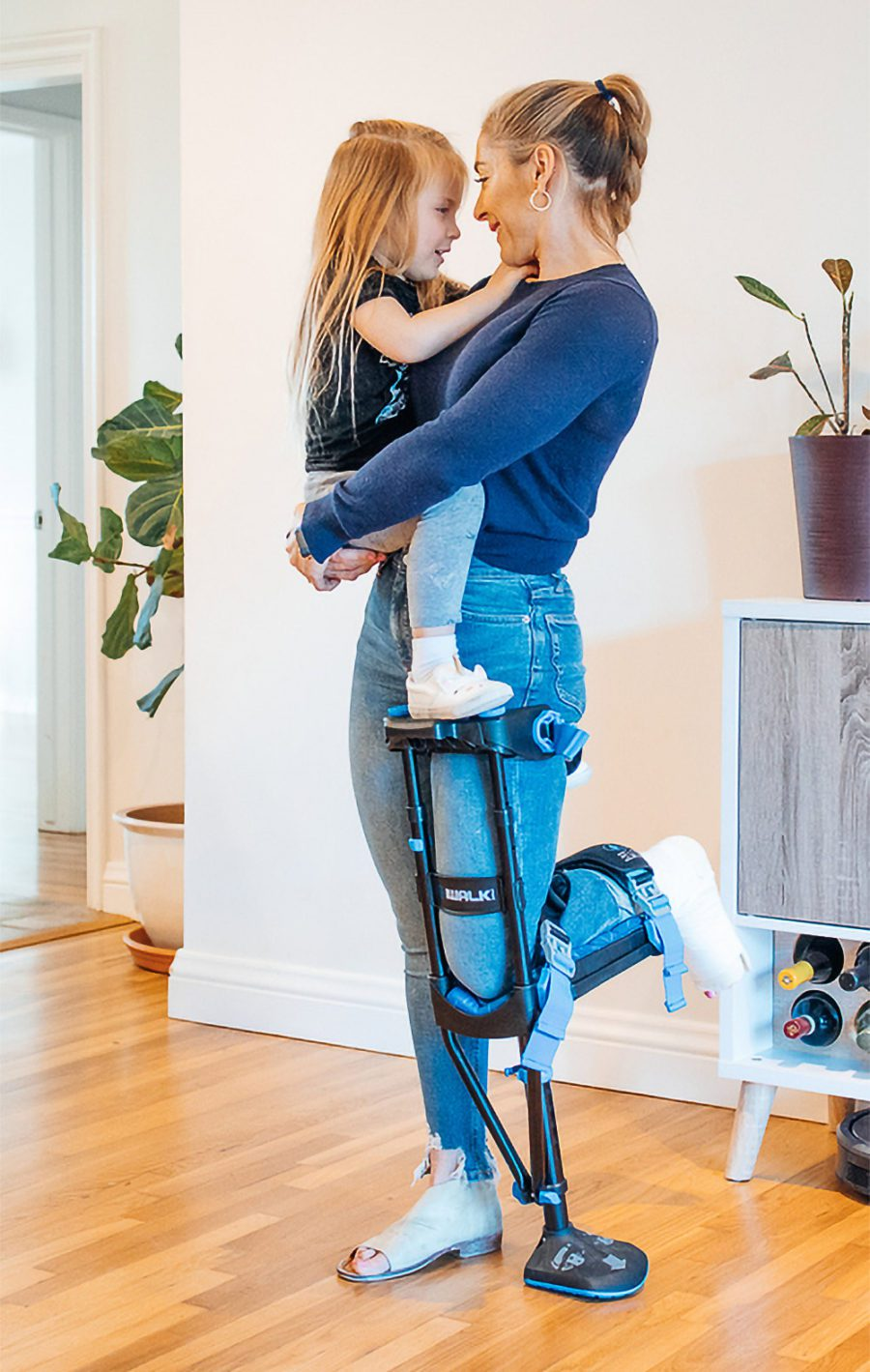 Woman with broken foot holding her child with iWALK3.0 crutch