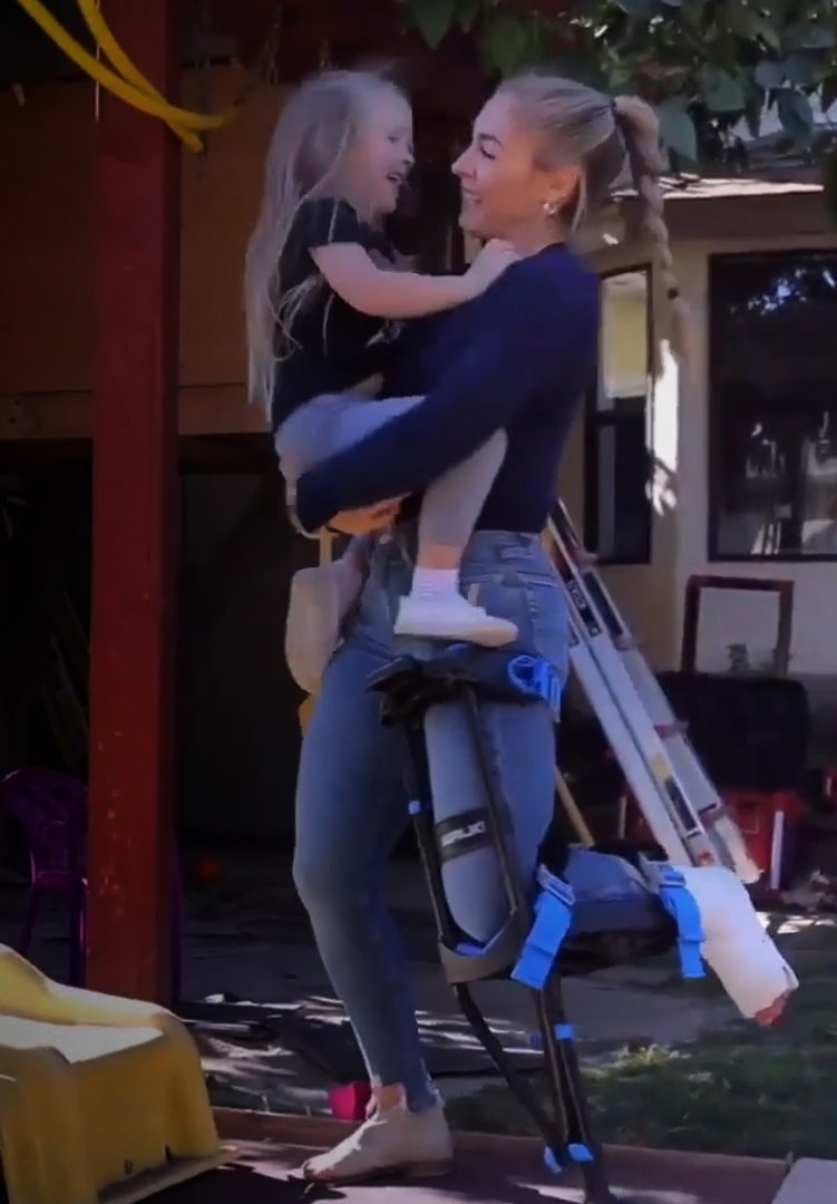 young woman with injured ankle holding child using iWALK3.0 crutch